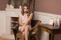 Beautiful girl sitting in a chair. By the fireplace Stock Photo