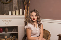 Beautiful girl sitting in a chair. By the fireplace Stock Photography