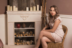 Beautiful girl sitting in a chair. By the fireplace Royalty Free Stock Images