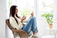 Beautiful girl sitting in chair looking at her phone while having a cup of coffee royalty free stock photo