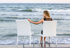 A beautiful girl is sitting on a chair and looking at the sea. The pretty young girl is sitting on the background of the sea. stock photos
