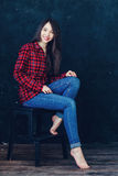 Beautiful girl sitting on a chair. In photo studio Stock Images