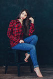 Beautiful girl sitting on a chair. In photo studio Stock Image