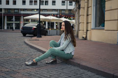 Beautiful girl sitting on a city street on curbing and looking forward. Stock Photography