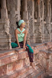 Beautiful girl sitting between the columns. A beautiful girl in sunglasses sits on a parapet between the pillars of an ancient temple Stock Image