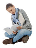 Beautiful girl sitting cross-legged, reading a book on a white Stock Image