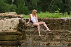 Beautiful girl sitting on the dam. Royalty Free Stock Images