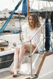 Beautiful girl sitting on the deck of a yacht Stock Photo
