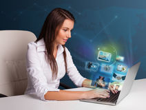 Beautiful girl sitting at desk and watching her photo gallery on Royalty Free Stock Image