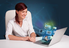 Beautiful girl sitting at desk and watching her photo gallery on Stock Images