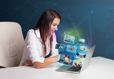 Beautiful girl sitting at desk and watching her photo gallery on Royalty Free Stock Photography