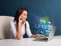 Beautiful girl sitting at desk and watching her photo gallery on Stock Photos