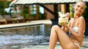Beautiful girl sitting at the edge of swimming pool Royalty Free Stock Photography