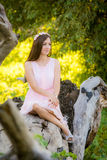 Beautiful girl sitting on fallen tree in the forest stock photos