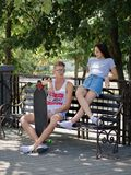 A couple of teens dating in a park, a beautiful girl and a fellow sitting on a bench on a natural blurred background. Stock Images