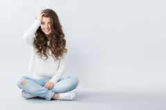 Beautiful girl sitting on the floor cross-legged. Teenager Royalty Free Stock Image