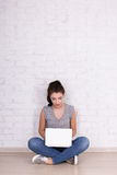 Beautiful girl sitting on the floor with laptop and space over w Royalty Free Stock Photography