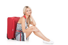 Beautiful girl sitting on floor with luggage. Royalty Free Stock Photo