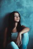 Beautiful girl sitting on the floor near the wall Stock Photos