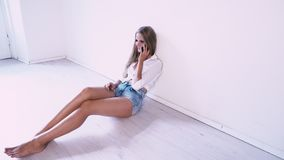 Beautiful girl sitting on the floor in a white room talking on the phone stock footage