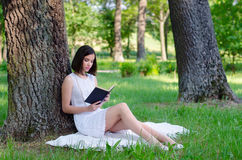 Beautiful girl sitting in forest and reading book in summer Stock Photo