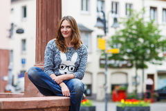 Beautiful girl sitting on fountain in german city Royalty Free Stock Photos