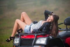Beautiful girl sitting on four-wheeler ATV Stock Photography