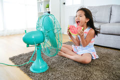 Beautiful girl sitting in front of electric fan. Beautiful youth girl holding watermelon sitting in front of electric fan and blowing cool fan for eliminating stock photos