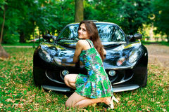 Beautiful girl is sitting in front of sport car Royalty Free Stock Photography