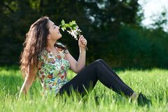 Beautiful girl sitting on a glade in the park, bright sun and shadows on the grass Royalty Free Stock Photo
