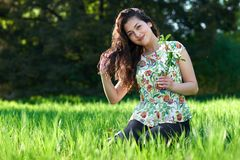 Beautiful girl sitting on a glade in the park, bright sun and shadows on the grass Royalty Free Stock Images