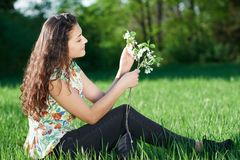 Beautiful girl sitting on a glade in the woods, bright sun and shadows on the grass Stock Photography
