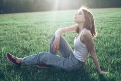 Beautiful girl sitting on the grass. Beautiful girl in jeans and white shirt sitting on the grass Stock Photo