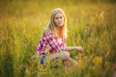 Beautiful girl is sitting in the grass Stock Photo