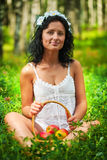 Beautiful girl sitting on grass floor and holding basket of appl Stock Image