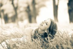 Beautiful girl sitting on grass in a park. stock images