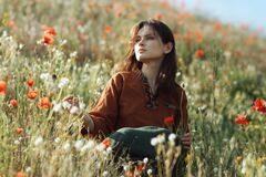 Beautiful girl sitting in the grass and poppies