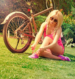 Beautiful girl sitting on the grass and tying laces Royalty Free Stock Images