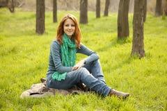 Beautiful girl sitting at green grass at park. Royalty Free Stock Photos