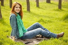 Beautiful girl sitting at green grass at park. Stock Photography