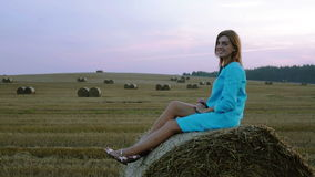 Beautiful girl sitting on a haystack, looking at the camera and sending air kiss. Side view. Large field with haystacks stock video footage