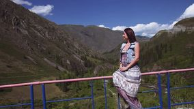 A beautiful girl is sitting at a height and admiring the beautiful nature. The mountains. Forest. A beautiful girl with long hair in a dress sits at the height stock video footage