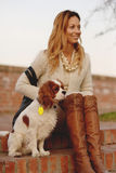 Beautiful girl is sitting with her dog Cavalier King Charles Spaniel on the red brick stairs Stock Photo