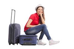 Beautiful girl sitting on her luggage Stock Photo