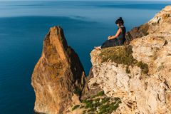 Beautiful girl sitting on a high rock and looking out to sea. Girl sits on the edge of cliff. The girl of the sea. Seascape. Girl at sunset royalty free stock photos
