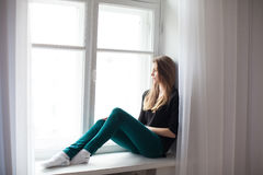 Beautiful girl sitting at home in front of a window Royalty Free Stock Photography