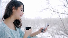 Beautiful girl sitting on Internet using smartphone and drinking tea at home near large window. Beautiful girl sitting on Internet using smartphone and drinking stock video footage