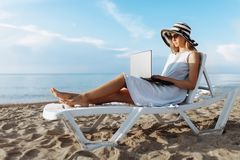 Beautiful girl sitting with a laptop on a chaise longue, a woman working on vacation, job search royalty free stock image