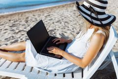 Beautiful girl sitting with a laptop on a chaise longue, a woman working on vacation, job search stock photography