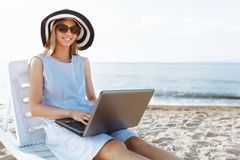 Beautiful girl sitting with a laptop on a chaise longue, a woman working on vacation, job search royalty free stock photography